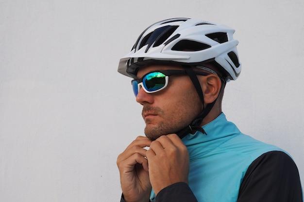 男のサイクリストは、乗る前にバイクのヘルメットをかぶっています。