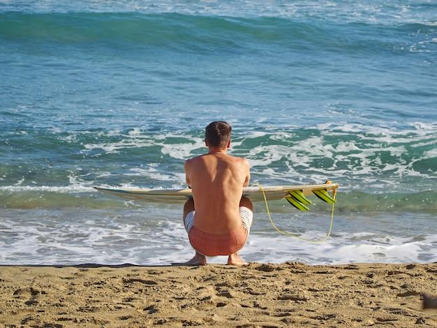サーファーがビーチに座ってサーフボードを持って波を見ています。