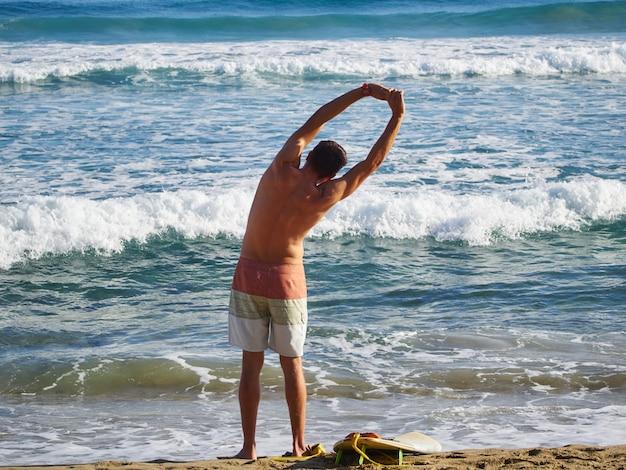 Человек серфер растяжения и разогрева перед серфингом. вид сзади. атлантический океан.