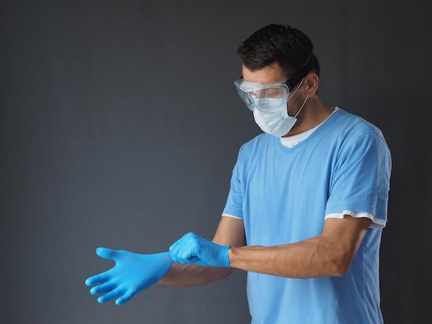 灰色の背景に青いラテックス手袋を置くフェイスマスクの男性医師。