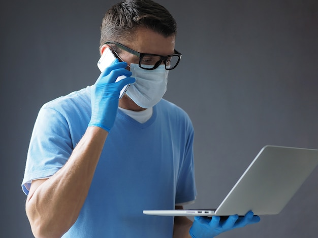 男性医師は携帯電話と彼のラップトップを使用してフェイスマスクを着ています。コロナウイルスの流行中に占領。