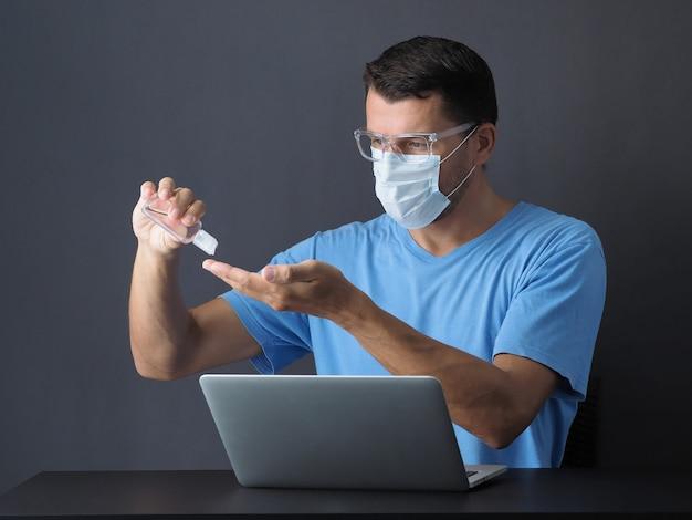 防護マスクを身に着けている検疫コロナウイルスの男性は、オンラインのラップトップで動作します。アルコールゲル消毒剤で手を洗って、手をきれいにしてください。