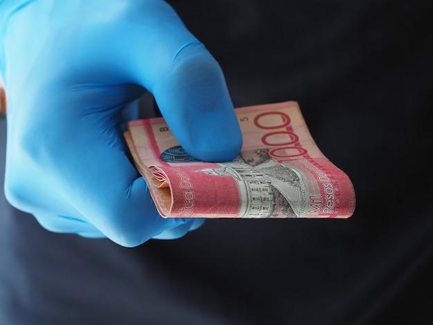 Крупный план. человек в синих перчатках держит деньги банкноты песо доминиканская республика.