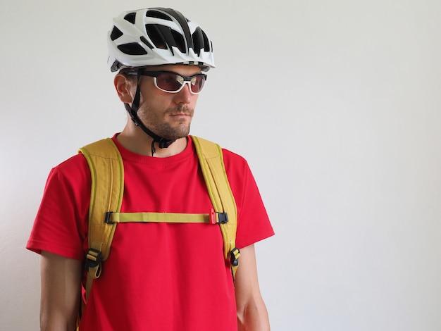 自転車の宅配便、黄色のバックパックの肖像画。ヘルメットとメガネの男。白色の背景。