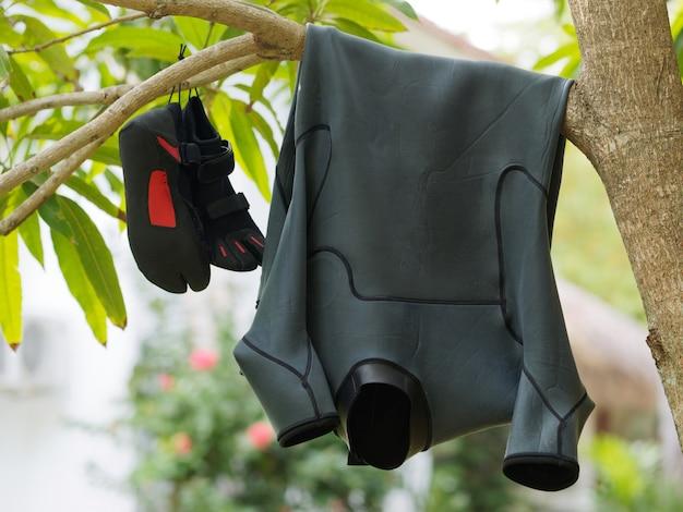 木の枝で乾燥するブラックサーフスーツとリーフシューズ。