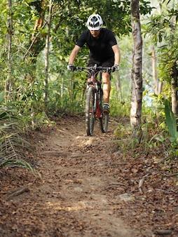 Человек спортсмен езда на велосипеде по лесной дороге.