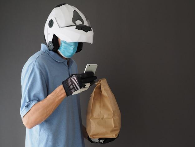 フードバッグとスマートフォンを保持している白いヘルメットと保護マスクを身に着けている宅配便。コロナウイルスのパンデミック時のコンセプトのフードデリバリー。