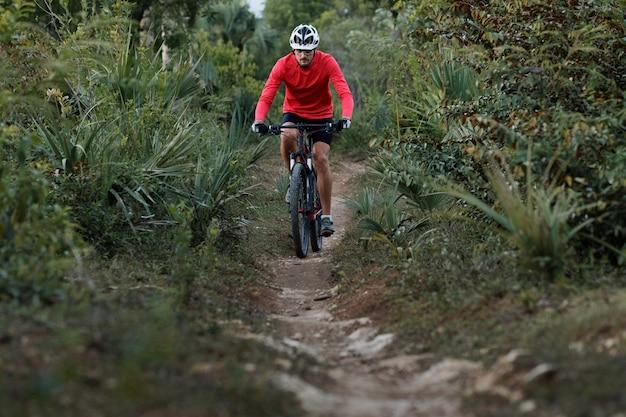 自転車用ヘルメットと赤いサイクリングジャージを着て、狭い歩道に乗るサイクリストの正面図。