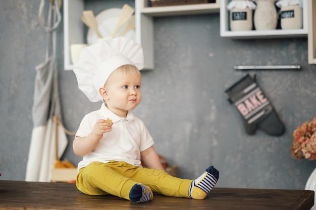 Один маленький мальчик в шляпе шеф-повара на кухне сидит на столе и ест