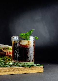 Стакан колы со льдом, мятой и розмарином на черном большом бутерброде
