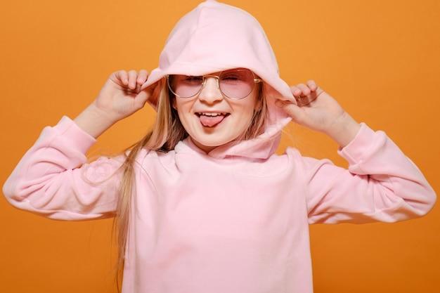 黄色のピンクの服のメガネとファッションモデルのブロンドの女の子
