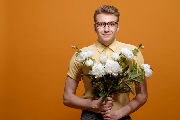 Доставка цветов, человек с цветами на желтом