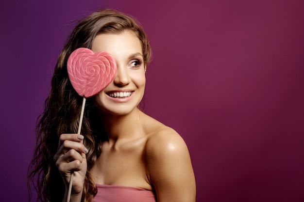 Модель девушка с сердцем валентина, концепция любви, улыбающаяся молодая женщина