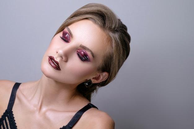 灰色の壁、きれいな肌と美しい唇とピンクのジャケットのファッションモデルの女性の美しさの肖像画は、深い紫色のスモーキーな目を作る