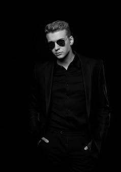 黒いジャケットに黒い眼鏡の若い男
