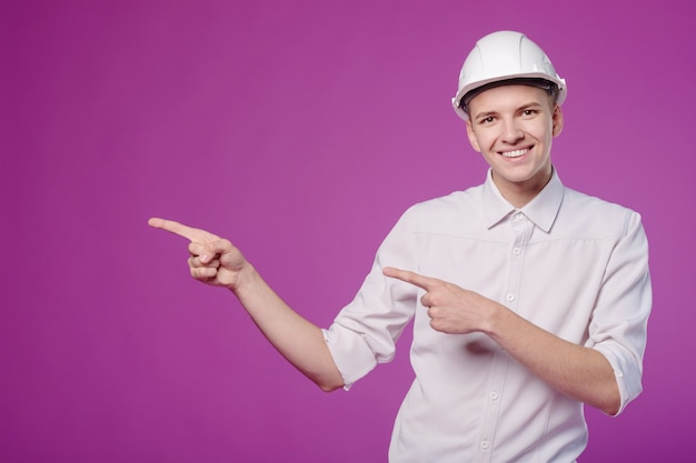 Молодой человек в белом шлеме с рабочим инструментом в руке
