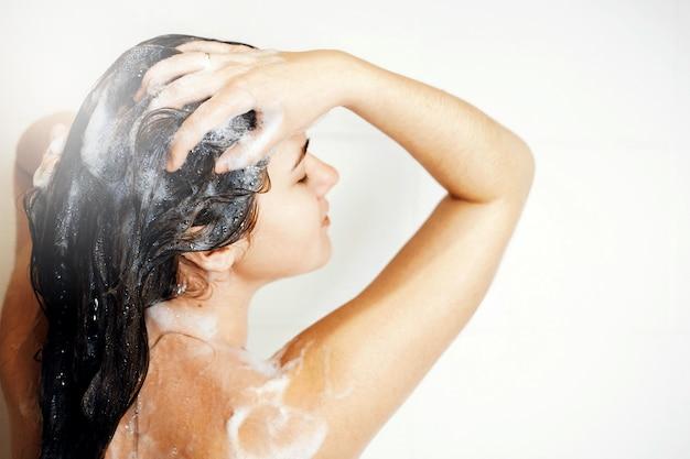 女性はシャワーで髪を洗う、シャワーを浴びる、蒸気が来る、髪に泡
