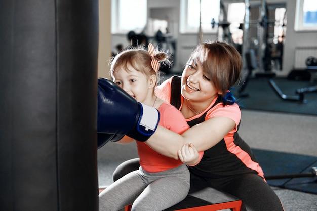 Маленькая девочка практикует бокс, девочка учит маму боксировать, забавную маму и дочь в спортзале, счастливую маму и дочь в спортзале