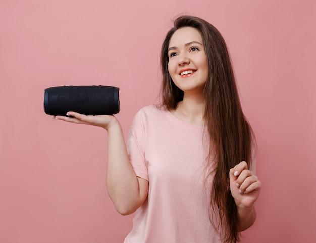 Молодая женщина с портативным динамиком в руке