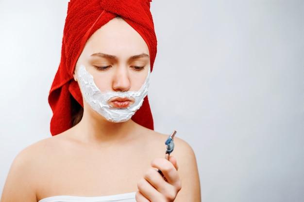 若い女性はかみそりでひげを剃る、女の子は彼女のひげの感情的な性別役割を剃りたくない