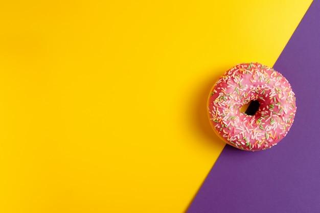 Розовый пончик на желтый и фиолетовый темно-фиолетовый фон вид сверху копией пространства