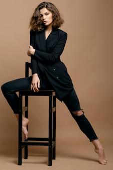 Модель красоты с чистой кожей и вьющимися волосами в черном пиджаке на бежевой стене на стуле, серьезная деловая женщина