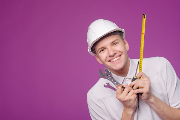 紫色の背景に手で作業ツールと白いヘルメットの若い男