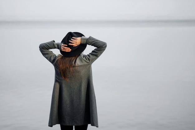 帽子、秋の海のビーチでのファッションモデルの魅力的な若い女性の美しさの芸術の肖像画