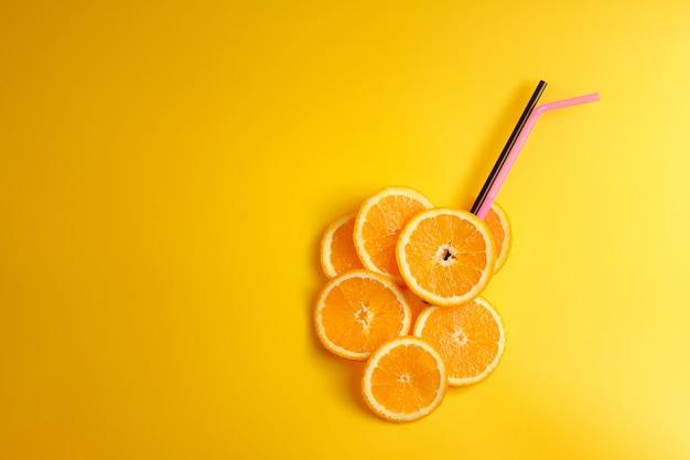 Ломтики апельсина, коктейльные трубочки, вид сверху, свежий апельсиновый сок