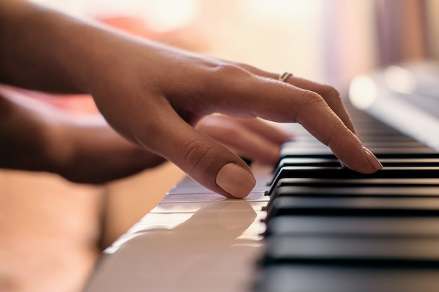 Женские руки играют на пианино