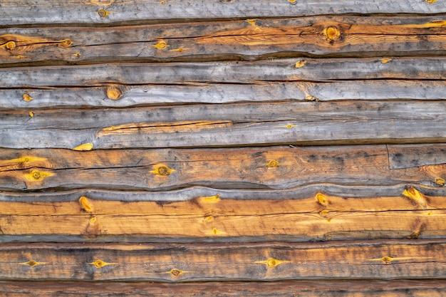 古い木製のひびの入った壁の表面。乾燥した木の質感