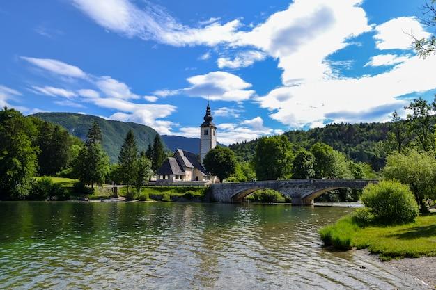 Церковь на берегу горного озера и старый каменный мост через реку.