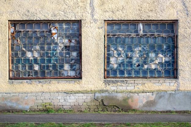 Два больших старых окна заброшенной фабрики. решетка на разбитых окнах.