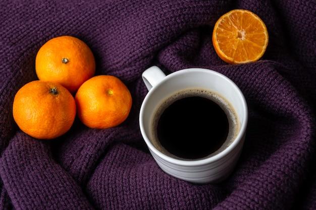 Белая кружка кофе и мандаринов на теплый фиолетовый вязаный свитер.