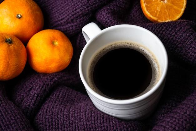 Мандарины и чашка кофе на теплом фиолетовом вязаном свитере