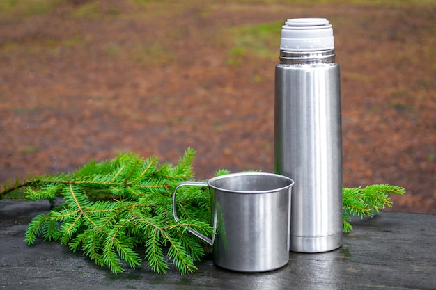 蓋が開いた魔法瓶と、その横にある金属製マグカップ。モミの枝を持つ木製の表面。