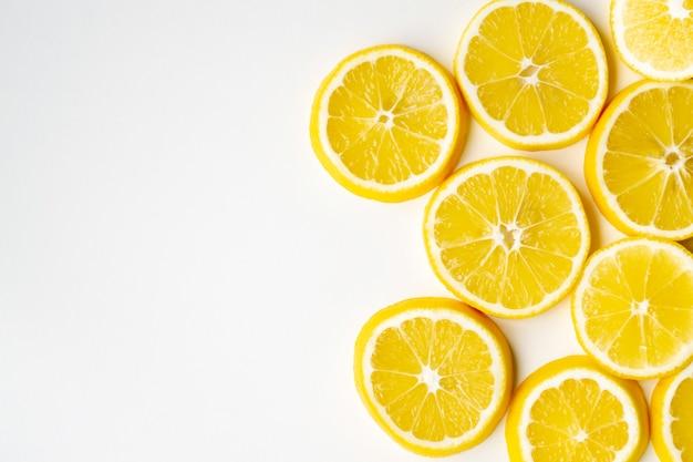Ломтики лимона случайно лежат на одной стороне на светлой поверхности стола. плоская планировка, крупный план.
