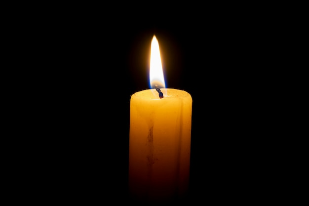 Горящая восковая свеча на черном фоне