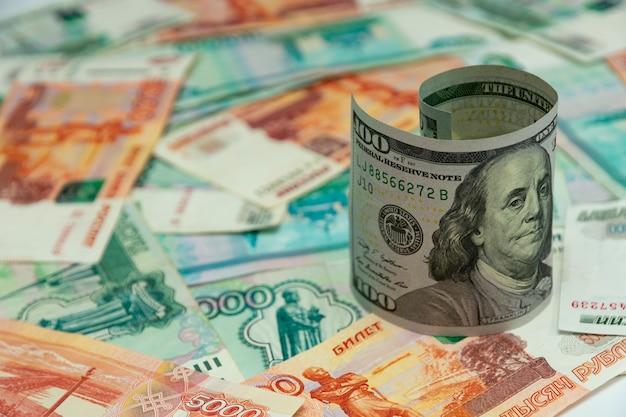 Витая стодолларовая банкнота на куче российских рублей, банкноты в тысячу и пять тысяч рублей