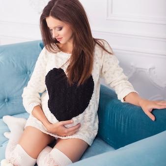 自宅でリラックスできる美しいブルネット妊娠中の女性