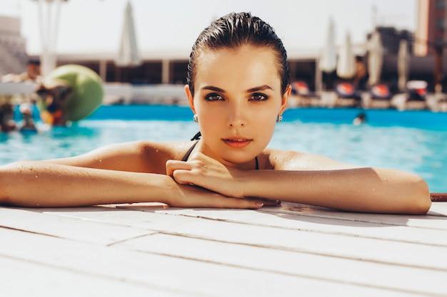 Красивая брюнетка женщина на пляже в бассейне один расслабляющий в купальнике. летом. на открытом воздухе
