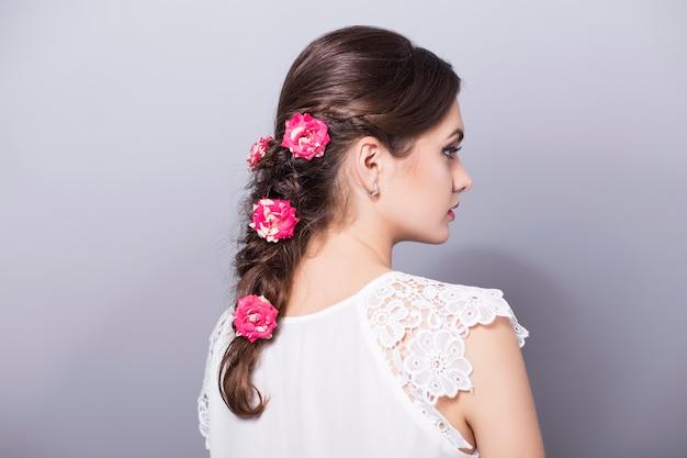 お下げの髪型と花を持つ美しい女性
