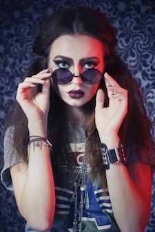 完全な唇、暗いメイクアップ、ロックスタイルの服、丸いサングラスと美しいブルネットの女性