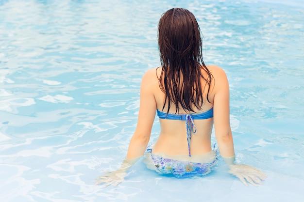 Брюнетка женщина в купальнике на бассейн один расслабляющий. лето. на улице