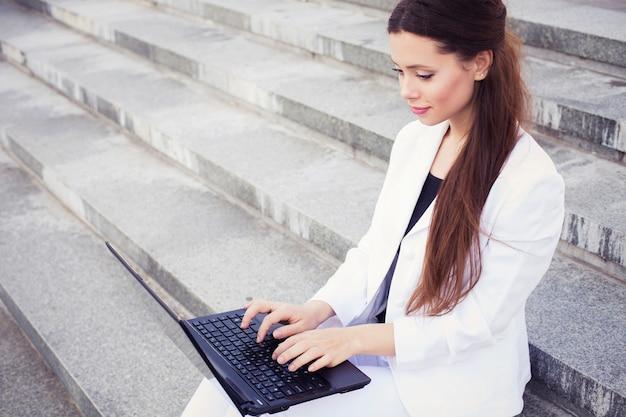 入力、屋外での作業、彼女の膝の上のノートブックと白いスーツのブルネットビジネス女性。コピースペース