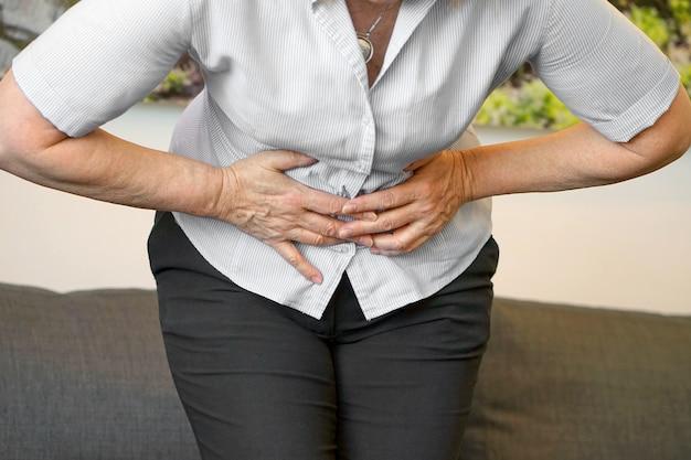 Взгляд крупного плана пожилой женщины имея тягостную боль в животе дома. хронический гастрит.