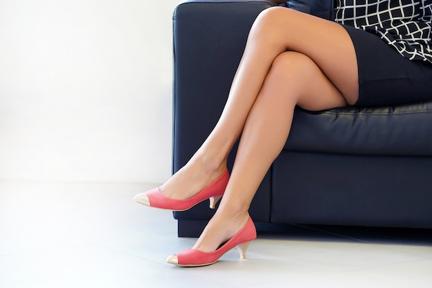 Крупным планом женские ножки в туфлях, сидя на диване. ноги женщины в красных туфлях на высоком каблуке, женщина сидит спокойно на диван, здоровье и красота ног концепции.