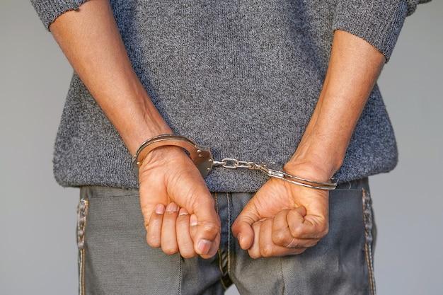 Преступные руки заперты в наручниках. крупным планом