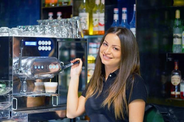 女性バーテンダーはカプチーノコーヒーのカップを注ぐ
