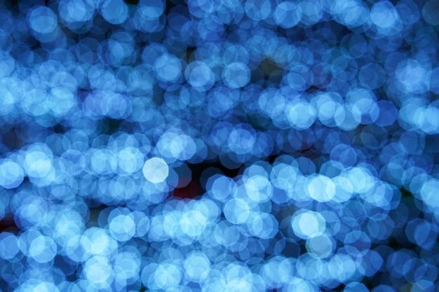 ボケクリスマスには、美しい光沢のあるクリスマスライトがぼやけています。抽象的なブルーのボケ